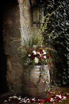 Old barrel with beautiful floral arrangement and petals on the ground