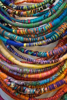 "Necklaces wrapped with fabric and thread - I've made one necklace like this but the grouping is stunning (found by ""gorgeous"" chandelier)......I want some bracelets like this!!!!"