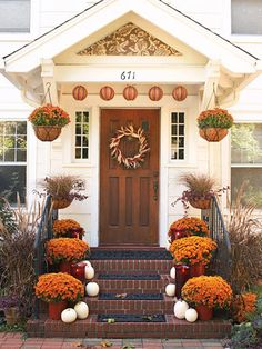Lush potted mums add color to this front stoop, as do paper lanterns hung from the portico. White pumpkins add contrast and a harvest wreath defines the solid wood door.