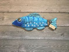 """Wood cutout FISH handcrafted in a unique """"folk art-industrial"""" style. Colorfully painted and decorated with a variety of washers, nails, wire & found objects. Each fish is given a name written on a whimsical wooden tag and are ready to hang inside or outside--and can even be displayed in the garden!"""