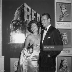 Israeli actor Haya Harareet and American actor Charlton Heston attend the premiere of director William Wyler's film 'Ben Hur,' in which they both starred, Hollywood, California. They stand in front of a promotional display for the film.