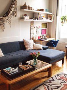 sofá em tons escuros e movéis de madeira deixam a sala sofisticada.