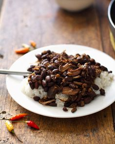 Crockpot Pork Adobo with Black Beans - Pork Adobo is a traditional Filipino dish with pork marinated and cooked in a soy sauce/vinegar sauce until it's super tender and completely saturated with flavor. The whole thing is usually scooped over a plateful of hot steaming white rice.