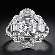 The sparkling 1.67 carat European-cut diamond shines like a headlight (with the brights on) from the center of this striking and magnificent original Art Deco platinum and diamond ring - circa 1930. The center diamond is embellished on all sides with eleven shimmering baguette diamonds amongst a dazzling array of small round diamonds.
