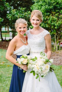 a bride and her bridesmaid hold classic bouquets of white and ivory.  the bridal bouquet is a clutch of white and champagne roses, green parrot tulips, white stock and white ranunculus.