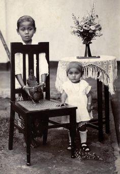 Peuter met favoriete kip / Favourite chicken Dochter (Willy Klaauwer , geboren 1924) van een Nederlandse KNIL-militair en een Javaanse vrouw in zondagse kleren op het erf voor haar huis , met haar tante (Jet Kasanpawiro) die haar lievelingskip voor haar vasthoudt. Tjimahi (Cimahi), West-Java, Nederlands-Indi련Indonesi멬 1926.