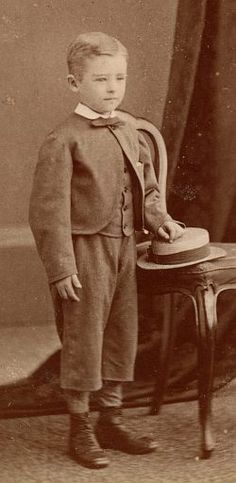 In a photo from 1874, the little boy wears a suit with a Zouave-style jacket, fastened only at the top and with a curved front exposing the waistcoat below. He has a small turn-over collar (fashionable at the time) and a narrow, small bow tie. He has 3/4-length trousers and stockings of a light color. The short trousers would evolve into the knee pants common in the 1880s and 90s. He wears leather lace-up high-top shoes. His left hand rests on a boater hat.