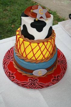 Simple cake - do one layer, mini cowboy plastic hat (walmart doll section!) and star (easy find), do the white frosting with cow spots, maybe a ribon around for color - red. base - easy cowboy scarf! perfect!