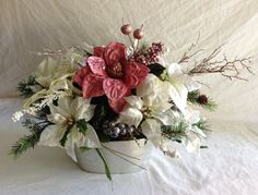 "This Victorian holiday flower centerpiece is a versatile piece of pure holiday cheer....designed to bring seasonal warmth to any room; in your home or office.  Arranged with silk flowers and surrounded with silver berries and pine branches in a silver flower pot.   A classic and elegant Christmas holiday centerpiece .. This arrangement will last you for many years to come.  etsy.com/mimiholt & FaceBook Designs By Mimi. Please visit my page and would love a ""like"" vote :)"