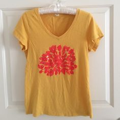 "J Crew v-neck tee Mustard yellow v-neck tee with coral print on the front. There is one stain on the front shoulder, but other than that it's lightly used. The tag says ""large"" but it fits more like a medium ☺️ super soft and cute to wear in the summer time (I just don't wear it that much anymore). J. Crew Tops Tees - Short Sleeve"