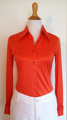 This is a cool 70s shirt in a bright orange and a tight stretch. The shirt is button front and has a large pointy collar perfect to wear with