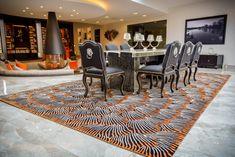 Bright orange patterned rug in a modern dining room #modernrug #diningroom #orangerug