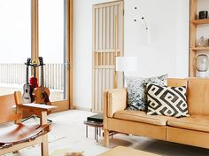 Warm living space with a camel leather sofa, printed throw pillows, and a wooden armchair