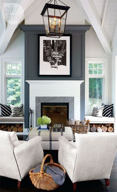 Living room, white chairs, fireplace, white beamed ceiling.  window seating on either side of the fireplace.