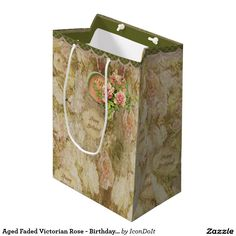 """Aged Faded #Victorian_Rose - Birthday - #personalized_gift_bag - The elegant and subtle design on this special #birthday_gift_bag features a profusion of creamy white & the palest of #pink_roses mossy green leaves and translucent opal badges w/the message """"Happy Birthday"""" in Olive Green script. A heart shaped emblem covered w/ pinker roses holds 2 custom text fields to personalize w/the recipient's initials (or clear to leave blank). Olive green w/ mauve lace border at top edge."""