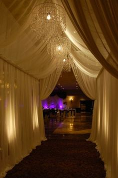 Dramatic but simple entryway. Beautiful pipe and draping with chandeliers and uplights.