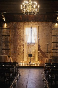 Curtain and hanging lights as backdrop. Love the elegance against the industrial setting.