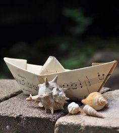 Paper sailboat and shells
