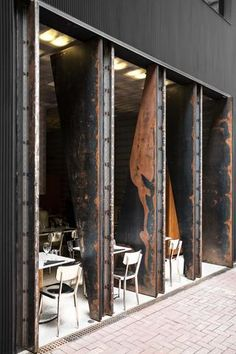 TUVE-Hong-Kong Oxidised metal doors, raw brass, grey flecked marble, textured concrete, gold leaf and wire glass work in harmony to create a rough yet pure aesthetic. Experimentation with lighting adds to the effect, enhancing the qualities of the materials through shadow and reflection.