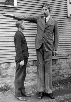 Robert Pershing Wadlow at age 13 stands with his father, Harold. Harold is 5 feet, 11 inches tall.
