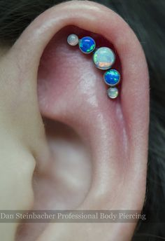 Helix piercing I did today atSaint Sabrina's.16g cluster with white opal and blue opal gems fromANATOMETAL.