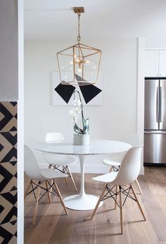 cute, simple white dining space with black & white art, a gold lantern & mid century classics