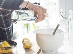 A DIY cleaner - water vinegar lemon juice - windows - is made in a white bowl.