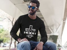 """Our signature Faith, Hope, And Love unisex, long sleeve t-shirt is a great reminder that we have already been given the most precious gift that there ever will be - Love! """"And these three remain: Faith, Hope and Love. But the greatest of these is love."""" 1"""