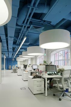 Offices with an exposed ceiling - air conditioner pipes and all services are seen but painted in a blue colour. Since Gypsum soffit ceilings were not done large round suspended light fittings with diffusers are hung over the desks and workstations