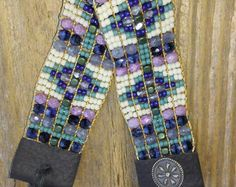 hand woven BOHO Beaded Bracelet 1.inch wide 6.5 inches in length. This Beautiful One of a Kind piece is composed of a very Carefully selected mix of hematite ,Japanese seed beads&Czech glass.This FLEXIBLE,SOFT & COMFORTABLE BRACELET is Meticulously Hand Woven on a Native American OJIBWA Loom by Artist Sherri Tremain Owner of Adornments925. This Piece Is sure To Last & Provide You With both Comfort & Durability. With Its 1940s Wheat Penny Hand Made Button and Reclaimed 100% ALL...