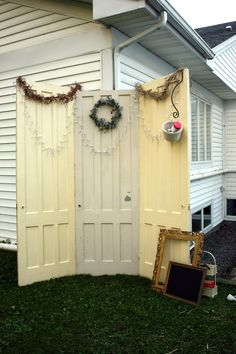 photo booth with old doors, white lights, chalk board and picture frame