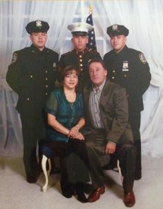 A family photo of Omar Rendon, in the rear center wearing a Marine uniform, flanked by his two brothers, who are police officers.//Decorated Marine veteran beaten by two unidentified undercover police officers.