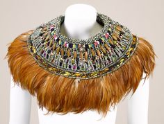 This piece explores the rich African artistry and craftsmanship and that of rich powerful, aristocratic glamour and pageantry of the seventeenth century characterized by high ruffled collars and bejewelled fabrics worn by Queen  Elizabeth I of England.  The jeweleries are designed with the articulated armour like look in mind, harnessed  with power and dominance, with finished looks filled with elegance and grace with an illusion of ease and comfort with lavishly trimmed frills, feathers…