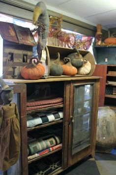 Prim Fall...cupboard with old quilts and prim pumkins. I need one of these...and the old quilts!