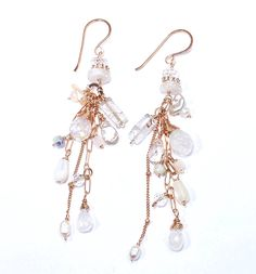 Rose gold filled satellite and paperclip chains dangle rainbow moonstone and sparkling clear natural zircon gemstone briolettes from these beautiful chains. Dangling with the briolettes are mother of pearl drops and cubes, mystic white opal rondelles as well as crystal quartz rectangles, keishi pearls and tiny rice pearls. Each earring also has a small round Swarovski crystal dangling for a dash of brilliant sparkle! All of these chains and gems dangle from rose gold filled rings and…