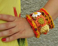 This unique handmade crochet bracelet is made of 100 % cotton thread. It is a shiny bracelet in boho style. Metal standard base is used to make the bracelet more stable.  The bracelet consists in seven different crochet flowers.  The main colors are three shades of yellow, orange, peach, beige, brown and white.  The bracelet is decorated with seed beads in yellow, dark orange, gold and brown. I also use natural stones like Tigers Eye, Agate, and Sunstone.  This cuff bracelet is a unique…