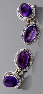 A pair of English Edwardian platinum and 15 karat gold cuff links with amethysts and diamonds. The cuff links have two cabochon amethysts with an approximate total weight of 19.60 carats, and 72 rose-cut diamonds with an approximate total weight of .32 carat. The amethysts are milligrain platinum set in an overlapping ribbon motif.