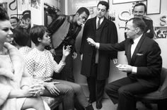 """<strong>Not published in LIFE.</strong> Sinatra offers a light in Davis' crowded <i>Golden Boy</i> dressing room in 1964. """"It was six a.m. before the party got to Frank's suite. But the evening was not over because Frank hadn't said it was over. 'Everybody have a little more gasoline,' he ordered. Everybody did."""" —<i>From """"The Private World and Thoughts of Frank Sinatra,""""</i> LIFE<i>'s classic photo-essay on the superstar, published in April 23, 1965</i>"""