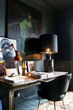 dark accent wall, light furniture, oversized lamp, stacked art, modern chair.