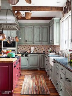 multicolored rug on a wooden laminate floor, inside a shabby chic kitchen, with rustic vintage duck's egg blue cupboards, and a red kitchen island