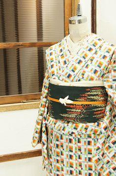 生成り色をベースに、ネイビー、オレンジ、ポピーレッド、スプリンググリーン、エバーグリーンなどのカラフルカラー愛らしいエルマーの絵本のようなモザイクチェックデザインが織り出された正絹紬の袷着物です。