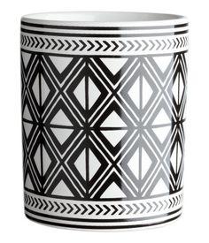 Valkoinen/Mustakuviollinen. Kivikeraaminen, painokuvioinen hammasharjamuki. Halkaisija 7,5 cm, korkeus 9 cm.