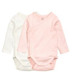 Light pink/dotted. CONSCIOUS. Wrap-front bodysuits in soft, organic cotton jersey with long sleeves. Snap fasteners at side and gusset.