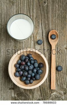 Top view on wooden bowl of fresh blueberries, wooden spoon and glass of milk on old wooden table by Natasha Breen, via Shutterstock