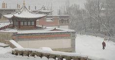 Monge budista tibetano percorre templo na província chinesa de Qinghai durante dia de neve e frio.