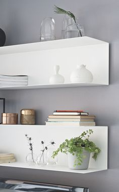 ikea white floating shelves on gray wall.