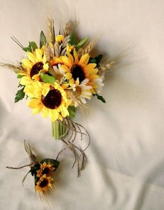 The bouquets will be a combination of yellow sunflowers, white daisies, dried wheat, and green lemon leaves, with the bridesmaids being slightly smaller.  The Maid of Honor's bouquet will feature a single hidden cream rose.