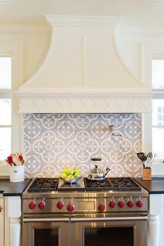 Stunning kitchen features an ivory French range hood suspended over a gray quatrefoil tiled backsplash lined with a swing arm spigot pot filler and a Wolf Range.