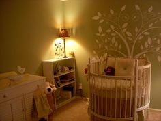 Eye Catching Baby Crib Design Play with Hues: Comfortable Nursery Room With Green Wall Tree Wall Art Round White Crib And White Vanity Near White Shelves