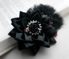 This black flower in the style of steampunk. Flower decorated with a black pen and a small red spider. This hairpin looks very attractive on the
